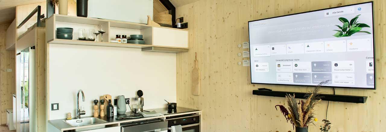 Küche mit Fernseher an Wand und geöffnetem Samsung SmartThings Dashboard