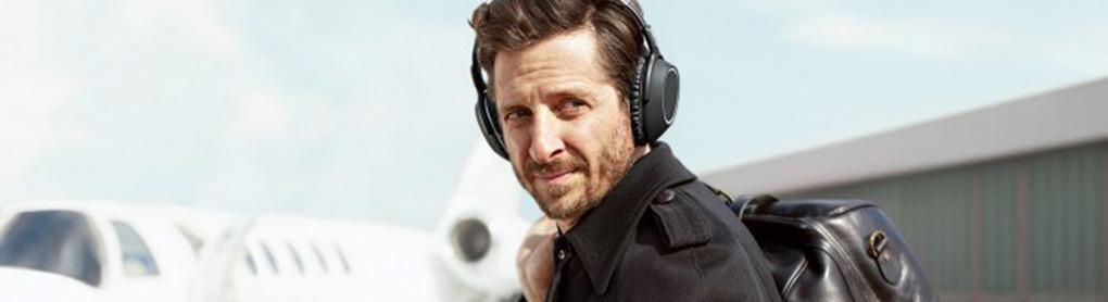 Mann mit Over-Ear-Kopfhörern schaut über die Schulter am Flughafen