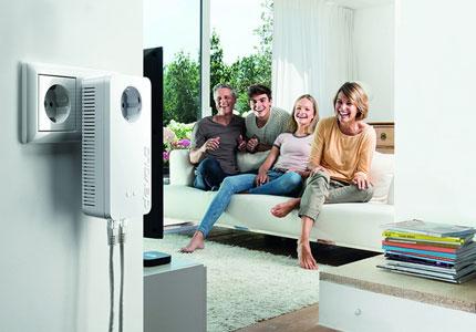 Glückliche Familie auf Sofa mit eingestecktem dLan-Stecker