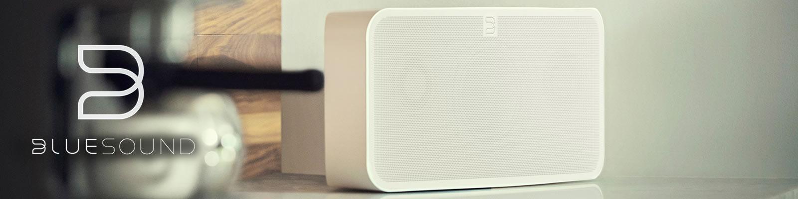 Smarter Bluesound Lautsprecher neben Bluesound Logo