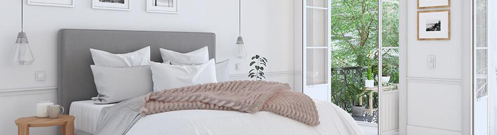 Schlafzimmer mit Doppelbett und geöffneten Glastüren zum Garten