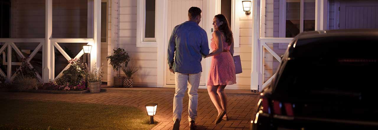 Paar geht durch ausgeleuchteten Vorgarten