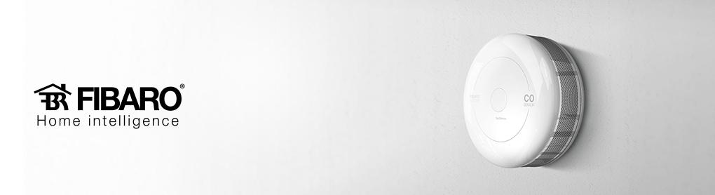 Montierter smarter Fibaro Rauchwarnmelder neben Fibaro Logo