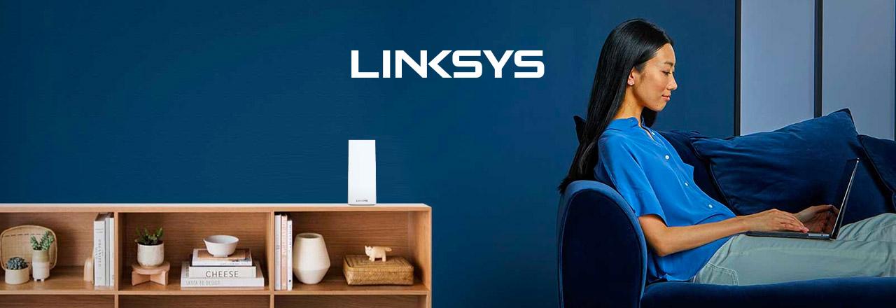 Frau mit Laptop auf Sofa mit WLAN Mesh System auf Sideboard und Linksys Logo