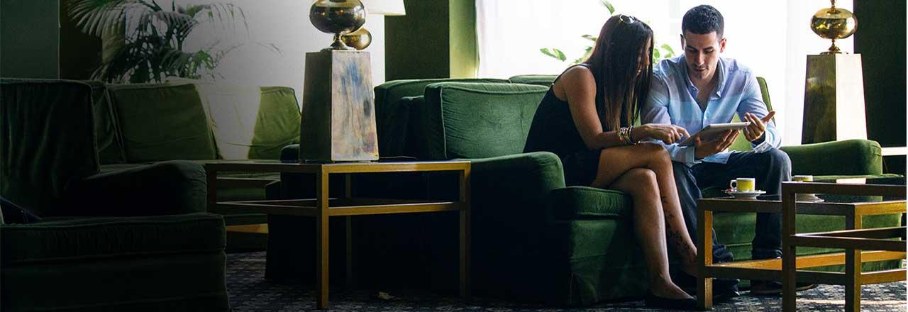 Mann und Frau mit Tablet auf grünem Sofa in Wohnzimmer