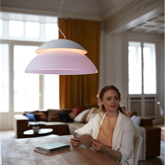 Philips Hue Beyond White and Color Ambiance LED-Pendelleuchte über einem Tisch hängend
