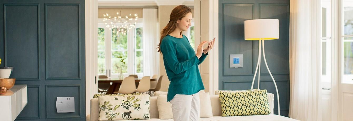 Frau steuert mit Smartphone Lupus Sicherheitsgertäe in Wohnzimmer