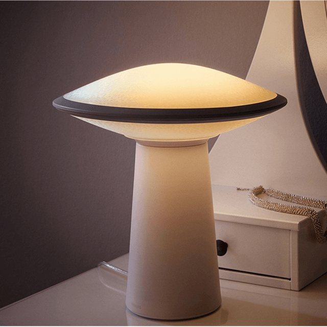 Philips Hue White Ambiance Phoenix Tischleuchte in weiß in dunkler Umgebung