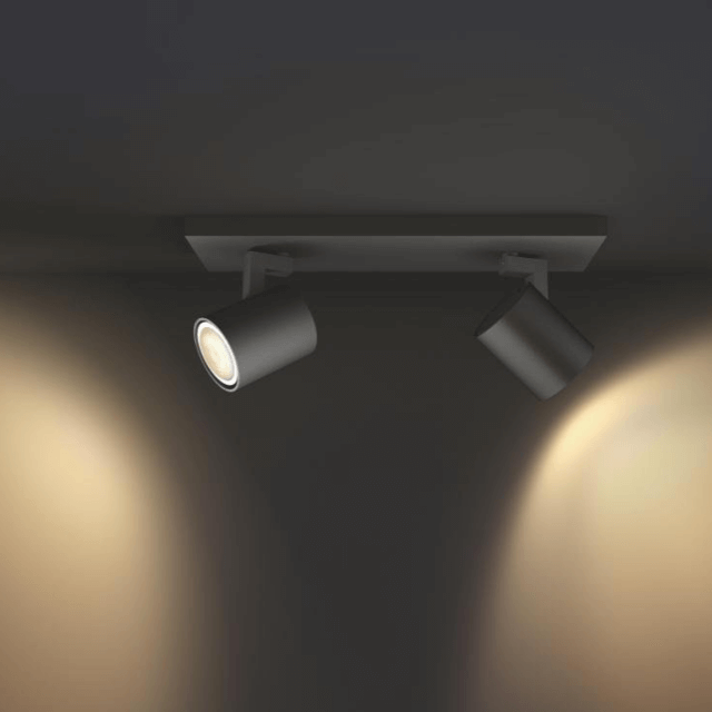Philips Hue Runner LED 2-er Spot 2x250lm in schwarz in seitlicher Ansicht in dunkler Umgebung mit gelbem Licht