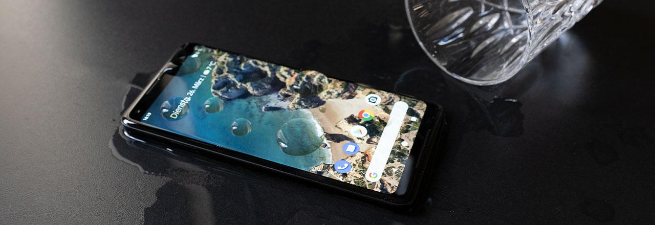 Google Pixel mit Wasser überschüttet neben umgefallenem Wasserglas