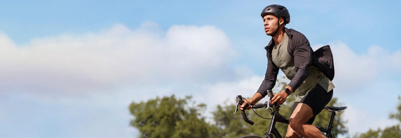 Mann auf Fahrrad mit Fitbit Sense