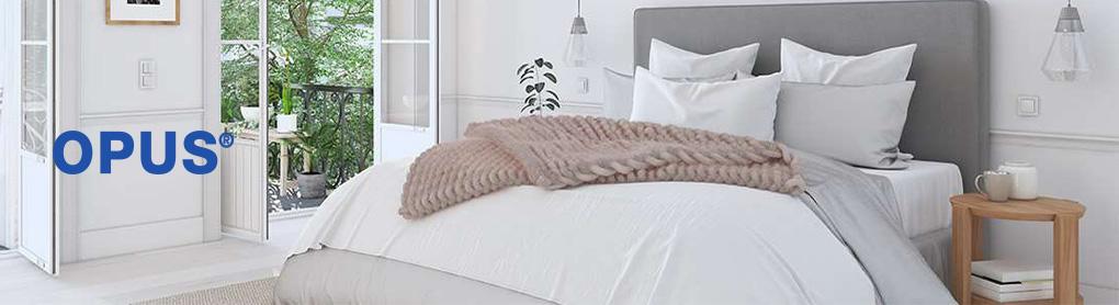 Schlafzimmer mit Doppelbett neben OPUS Logo
