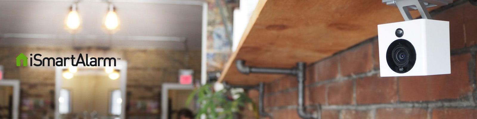 Nahaufnahme von installierter smarter Überwachungskamera neben iSmartAlarm Logo