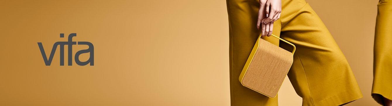 Frau hält smarten Vifa Lautsprecher neben Vifa Logo