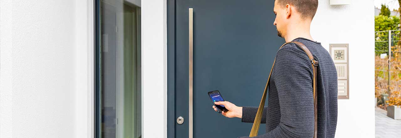 Über die HomeTec-App von ABUS öffnet ein Mann seine Haustür.