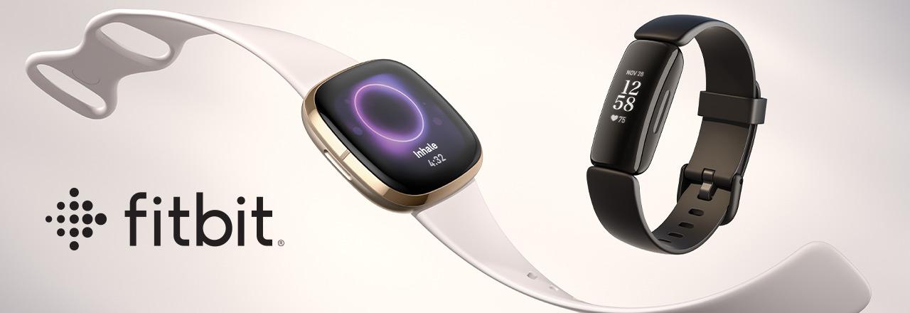 Fitbit Armband und Firbit Smartwatch neben Fitbit Logo