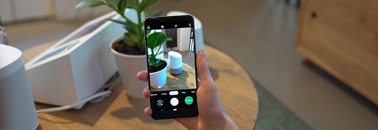 Jemand macht ein Foto von einem Google Home mit Google Pixel