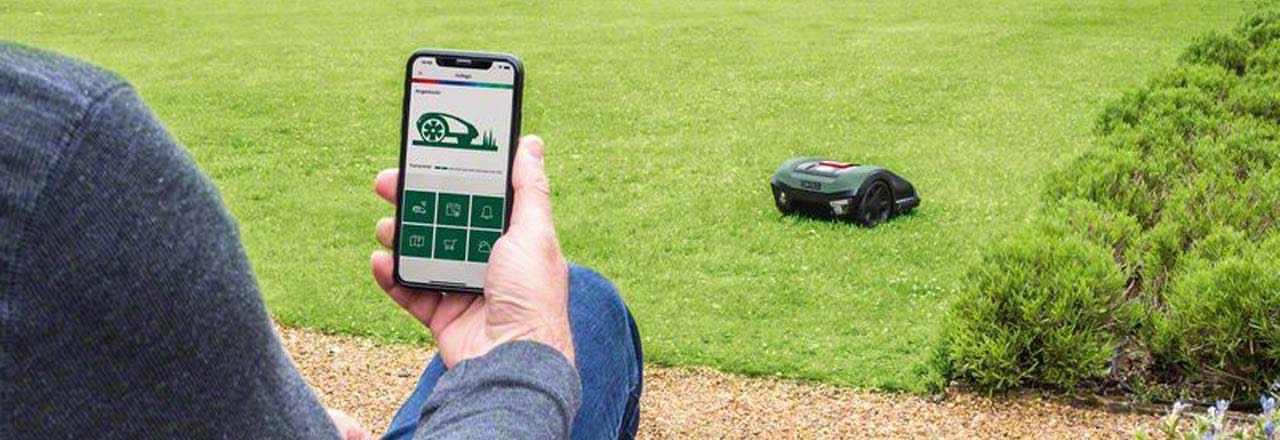 Mann in Garten mit Bosch Mähroboter und Bosch Smartphone App