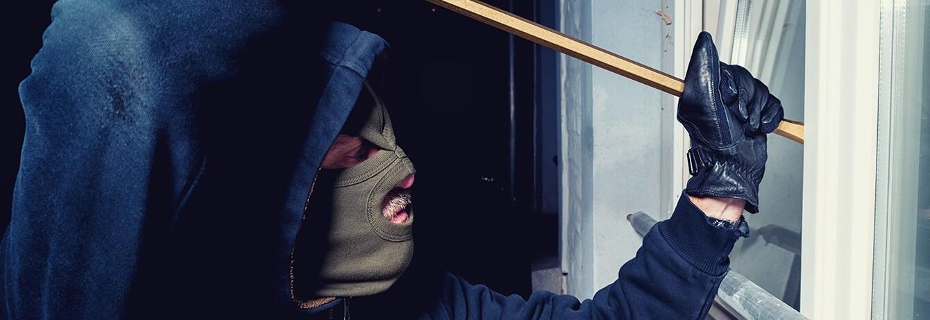 Mann mit Sturmmaske und Brecheisen an Tür- Versuch einzubrechen