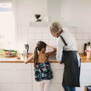 Elgato Eve Button in schwarz liegend auf Küchentisch mit kochenden Personen