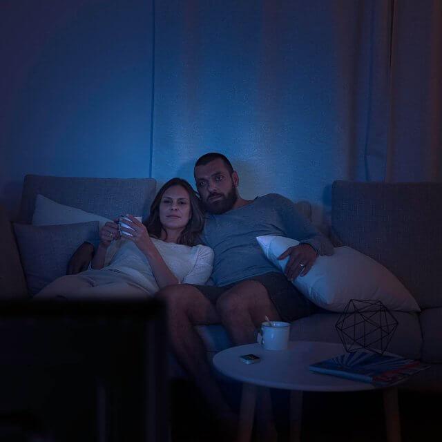 Elgato Eve Button in schwarz auf einem Tisch liegend mit im dunkeln fernschauenden Personen
