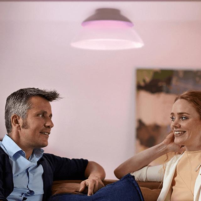 Philips Hue White and Color Beyond LED-Deckenleuchte an Decke angebracht mit Leuten im Vordergrund sitzend