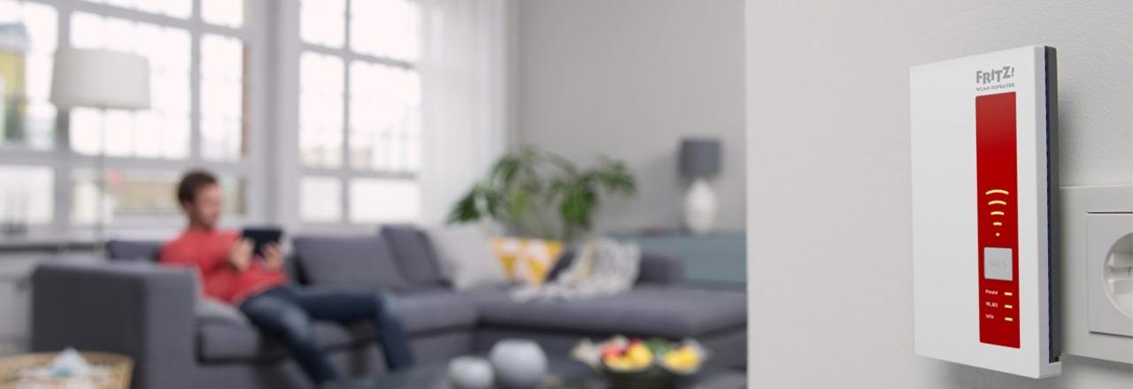 AVM FRITZ!Repeater in Steckdose mit Mann auf Sofa