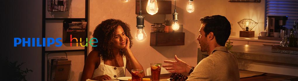 Mann und Frau am Esstisch mit gedimmten smartem Licht und Philips Hue Logo