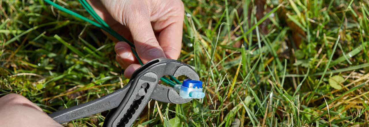 Jemand befestigt mit einer Rohrzange eine Kabelklemme im Garten