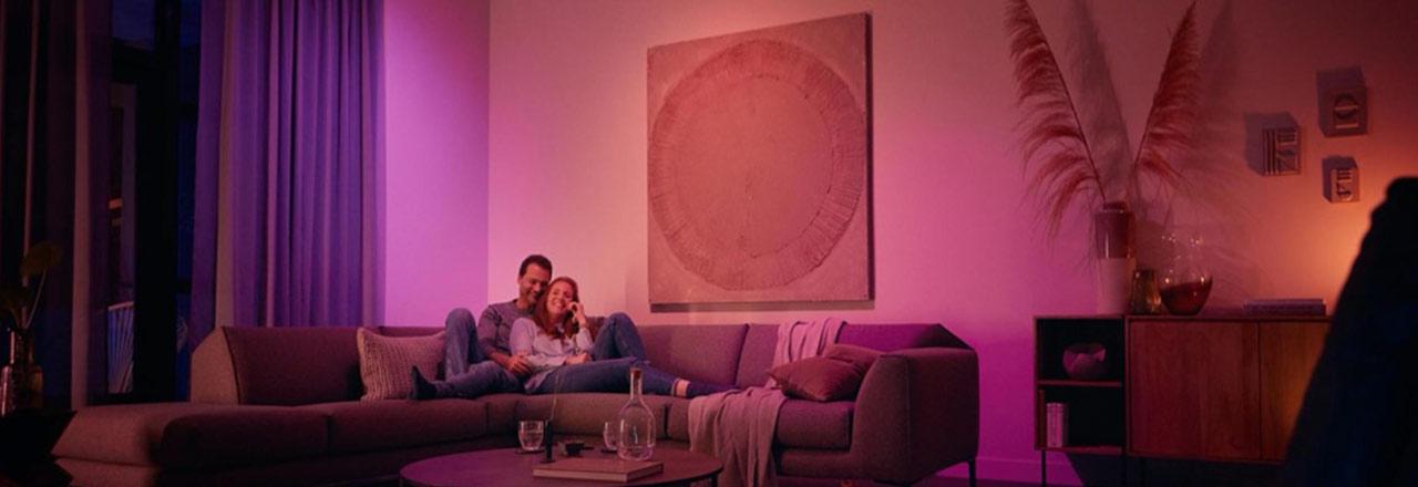 Glückliches Paar sitzt auf einem Sofa in farbigem Licht