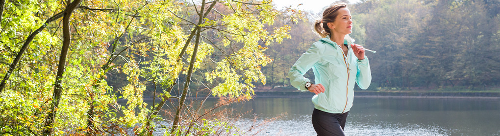 Frau mit Smartwatch joggt um einen See